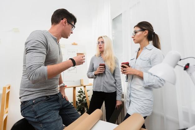 Socios comerciales sosteniendo tazas de café y mirándose