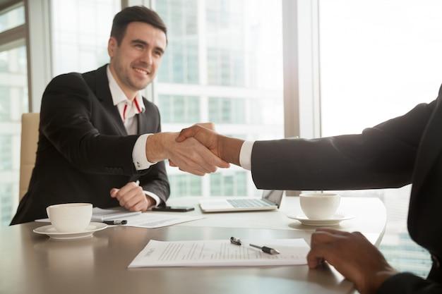 Socios dándose la mano después de cantar contrato.
