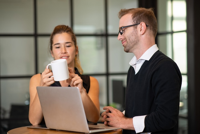 Socios de negocios tranquilos charlando y trabajando en la mesa de café.