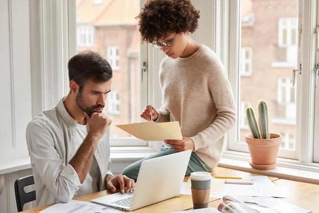 Los socios interraciales trabajan en un proyecto común en el espacio de coworking, discuten ideas, trabajan con papeles, están ocupados, toman café