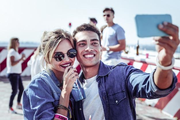 Socios jóvenes. hombre morena complacido demostrando sus emociones mientras hace una foto selfie