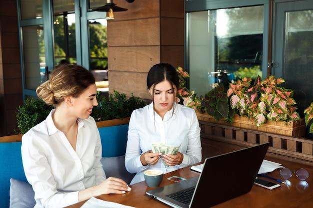 Socios de mujeres de negocios están trabajando en un café y contando dinero. concepto de éxito