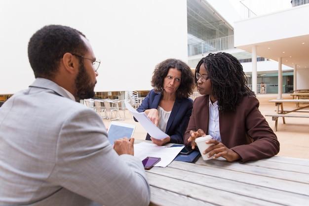 Socios multiétnicos discutiendo contrato en café al aire libre
