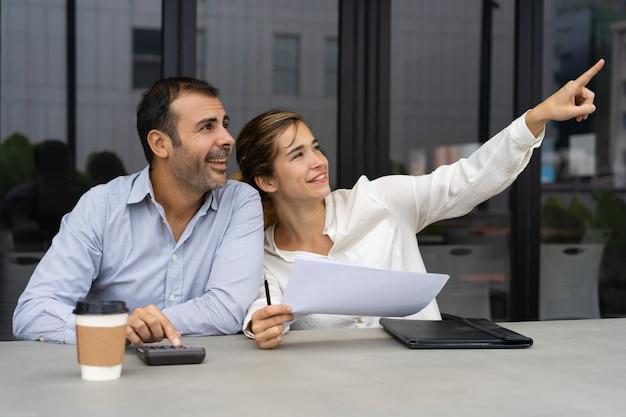 Socios de negocios alegres discutiendo inversión inmobiliaria