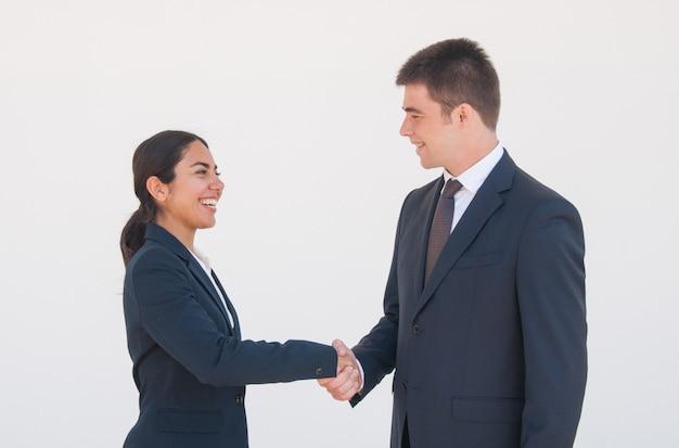 Socios de negocios alegres estrechándose las manos