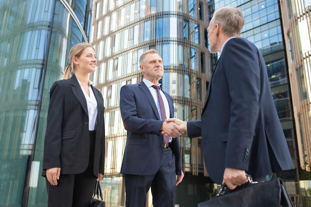 Socios de negocios confiados reunidos en la ciudad, dándose la mano cerca del edificio de oficinas. disparo de ángulo bajo. concepto de cooperación y asociación