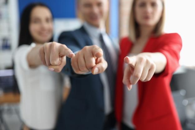 Socios de negocios exitosos señalando con el dedo delante de ellos closeup