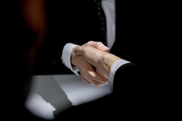 Socios de negocios haciendo apretón de manos en la sombra oscura