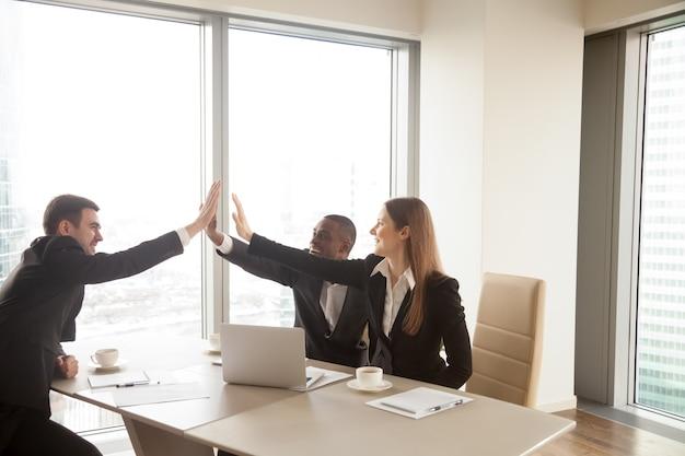 Socios de negocios multiétnicos que dan alta cinco en la reunión, cele