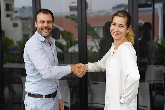 Socios de negocios positivos dándose la mano