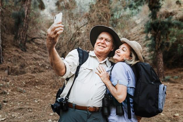 Socios senior tomando selfie en el bosque
