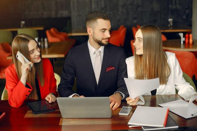 Socios sentados a la mesa y trabajando en un café
