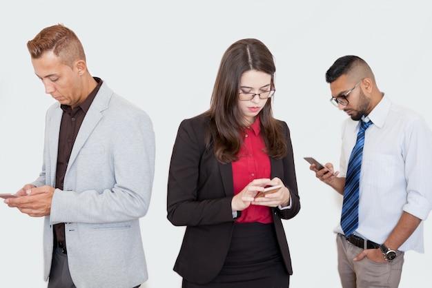 Socios serios que usan teléfonos inteligentes en la reunión