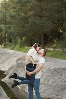 Socios de tiro medio besándose en la naturaleza