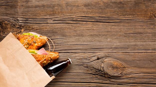 Soda y sandwiches en una bolsa de papel.
