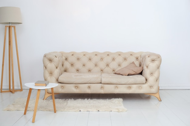 Un sofá beige con una almohada decorativa, una mesa de café y una lámpara en una espaciosa sala blanca. interior de la habitación espaciosa con un cómodo sofá contra una pared blanca. decoración del hogar. estilo escandinavo