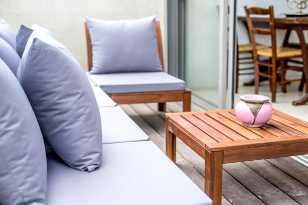 Sofá blanco con un entrenador y un diseño interior de mesa de madera.