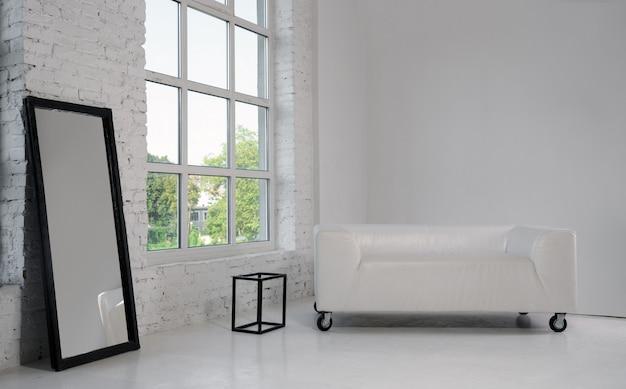 Sofá blanco y gran espejo negro enmarcado en sala blanca