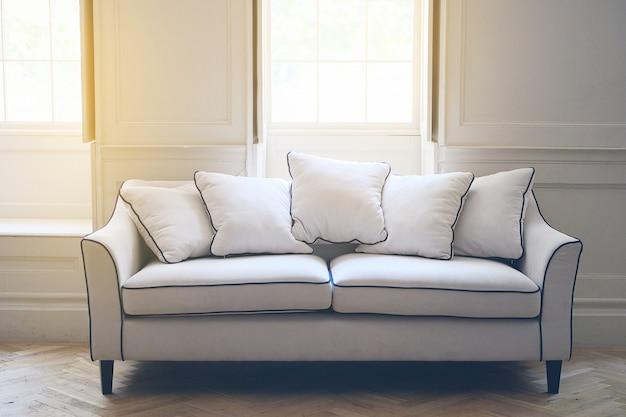 Sofá blanco en el interior al estilo inglés. la luz del sol entra a través de windows.