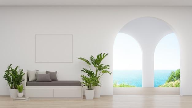 Sofá cerca del marco de imagen en blanco en la pared blanca.