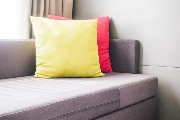 Sofá con cojines de color amarillo y rosa