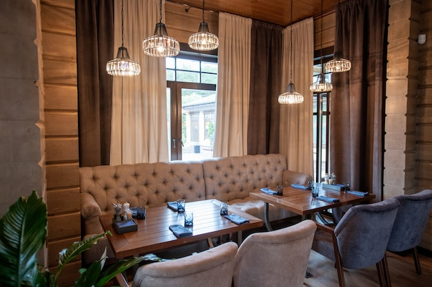 Sofá de cuero beige y sillones de terciopelo suave de pie junto a la mesa de madera preparada para los nuevos huéspedes del lujoso restaurante