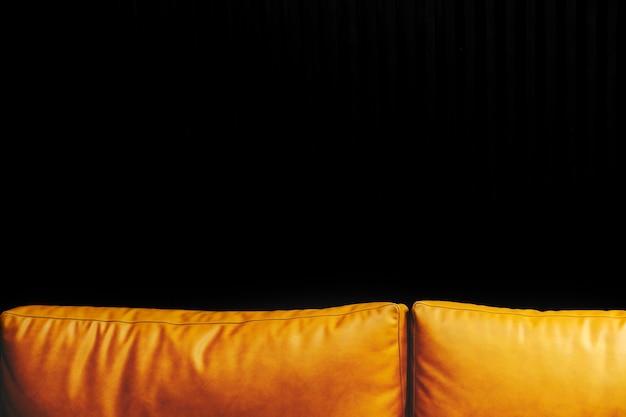 Sofá de cuero naranja contra una pared negra