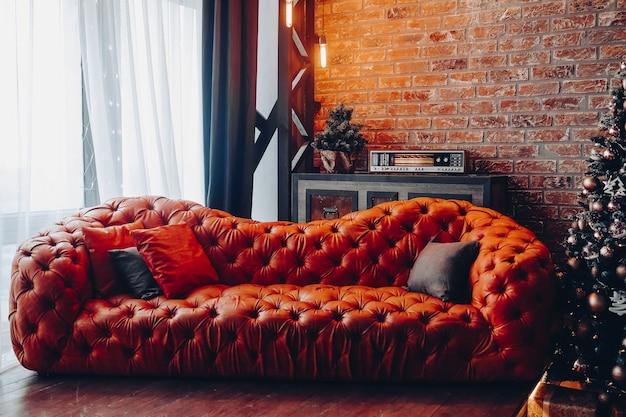 Sofá de cuero rojo de moda moderno con cojines. árbol de navidad recortado. pared de ladrillo. diseño loft.