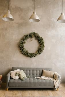 Sofá gris con almohadas y corona de navidad en la pared de la sala de estar