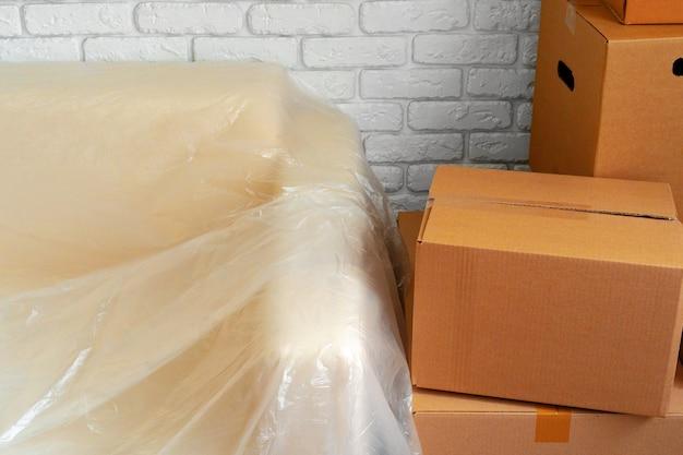 Sofá lleno y pila de cajas de cartón en una habitación. emocionante