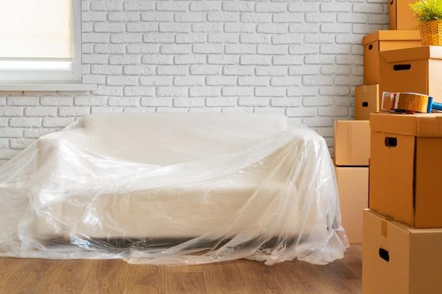 Sofá lleno y pila de cajas de cartón en una habitación.