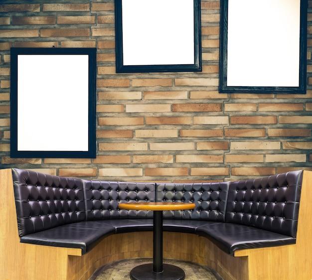 Sofá de lujo en el fondo de la pared de ladrillo con marco de fotos, galería interior