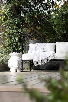 Sofá de madera al aire libre con cojines blancos.