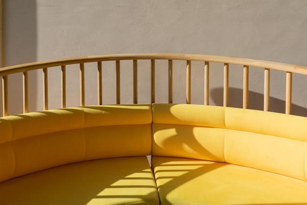 Sofá redondeado amarillo textil de cerca en día soleado