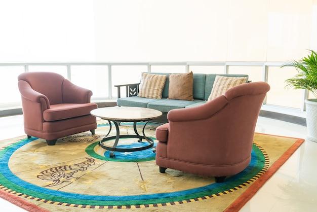 Sofá vacío y silla con decoración de almohadas en una habitación.