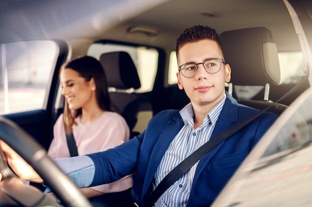 Sofisticada joven pareja caucásica feliz conduciendo en coche. hombre de la mano en el volante.