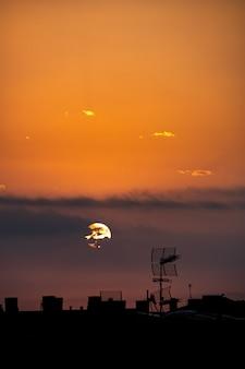 El sol aparece desde detrás de las nubes, sobre la ciudad, vista desde el techo.
