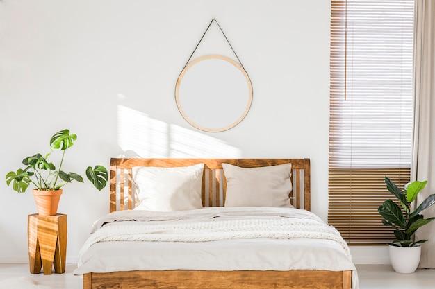 El sol brillaba sobre una pared blanca con un espejo redondo en el interior de un dormitorio minimalista con muebles de madera natural y hermosas plantas verdes