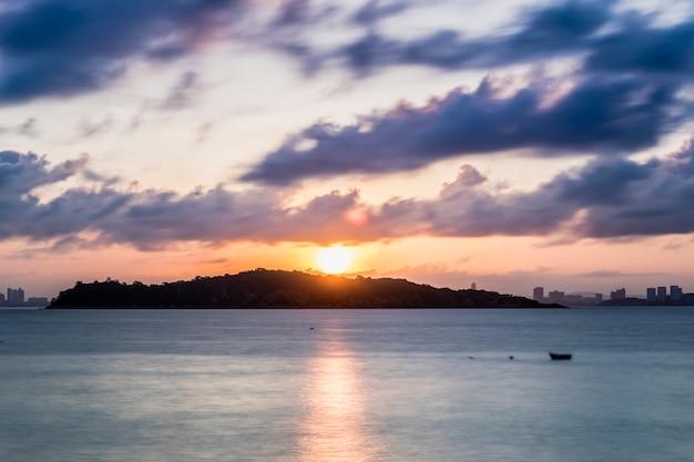 Sol y crepúsculo nube de movimiento en el mar