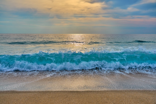 El sol detrás de las nubes se refleja en el agua y las olas con espuma golpean la arena.