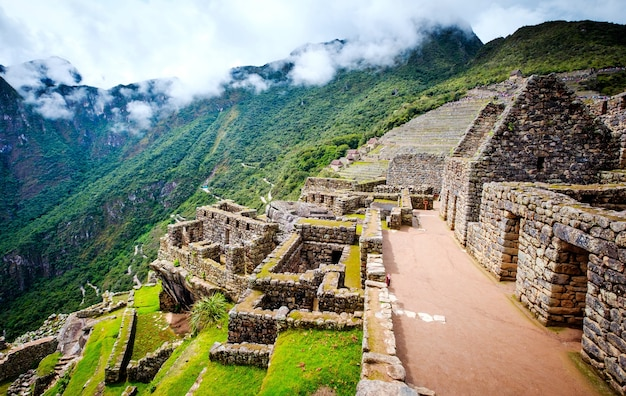 Sol impresionante vista de machupicchu muros de anclaje de piedra y templo entre montañas cubiertas de ...