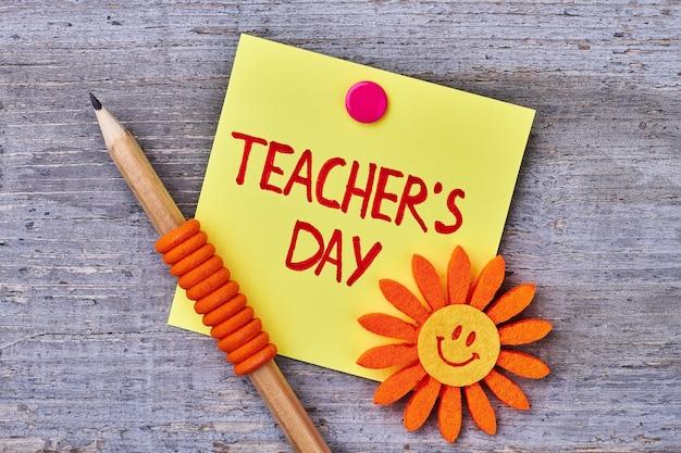Sol, lápiz y tarjeta decorativos. texto de felicitación del día del maestro.