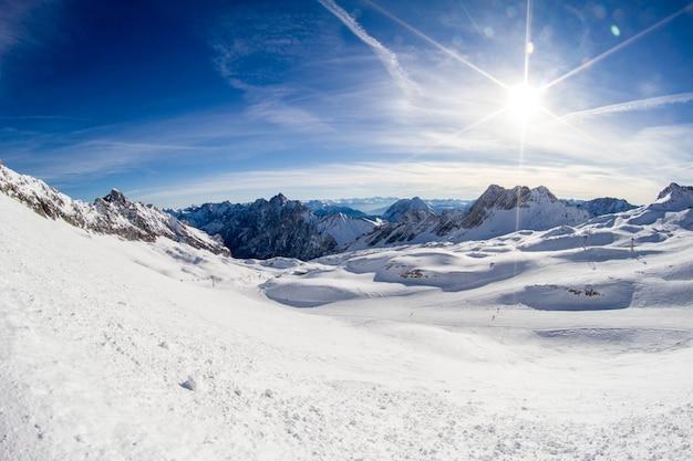 Sol en pista de esquí y panorama de los alpes nevados desde la estación de esquí