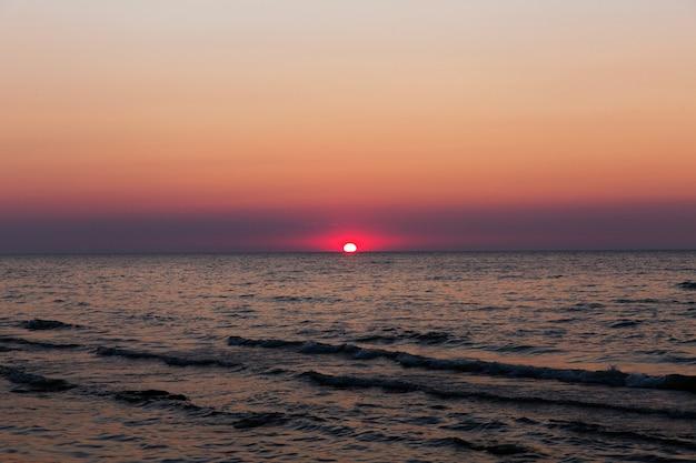 Sol rojo en una puesta de sol. atardecer en el mar. hermoso paisaje de la tarde. olas en un mar en una puesta de sol