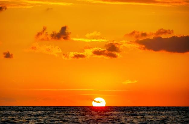 El sol tocó el horizonte al atardecer sobre el mar.
