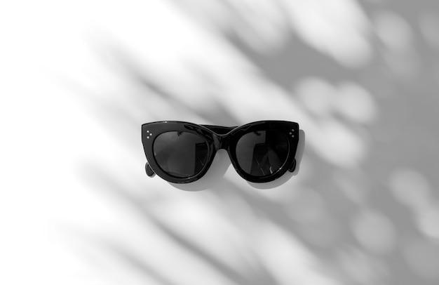 Sol de verano con sombra de hoja de palma con gafas de sol de moda sobre fondo blanco.