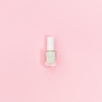 Sola botella de esmalte de uñas blanco sobre fondo rosa