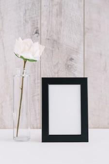 Sola flor blanca en florero cerca de marco de imagen en blanco