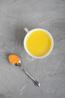 Sola taza de leche dorada india servida con una cuchara de cúrcuma en polvo sobre fondo de hormigón gris