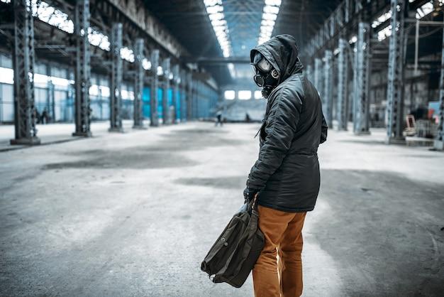 Soldado acosador, hombre con máscara de gas en edificio abandonado.